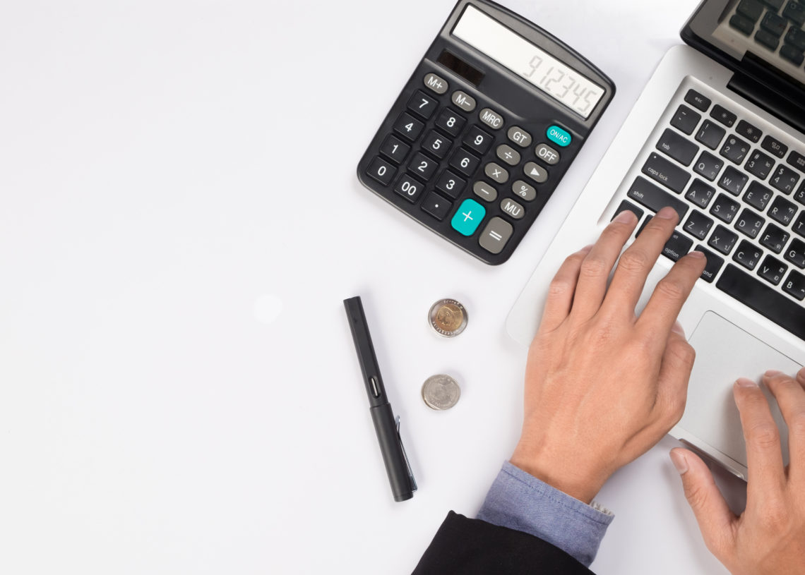 Businessman with laptop and the calculator counting the cash flow
