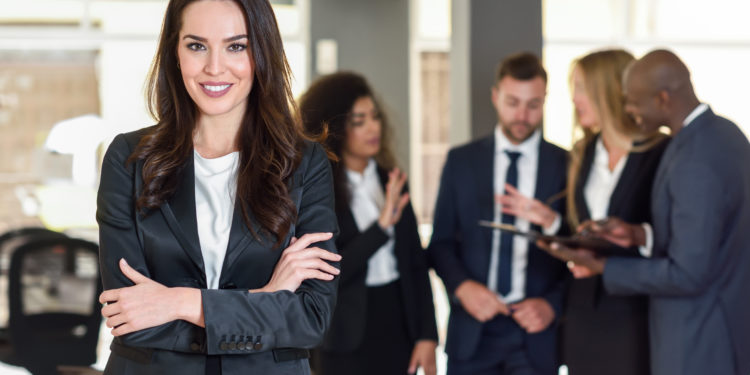 Business woman in black suite standing at the meeting with other men