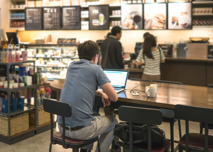 Work At A Coffee Shop With An Independent Laptop That Connects To The Internet Through Light. Computer