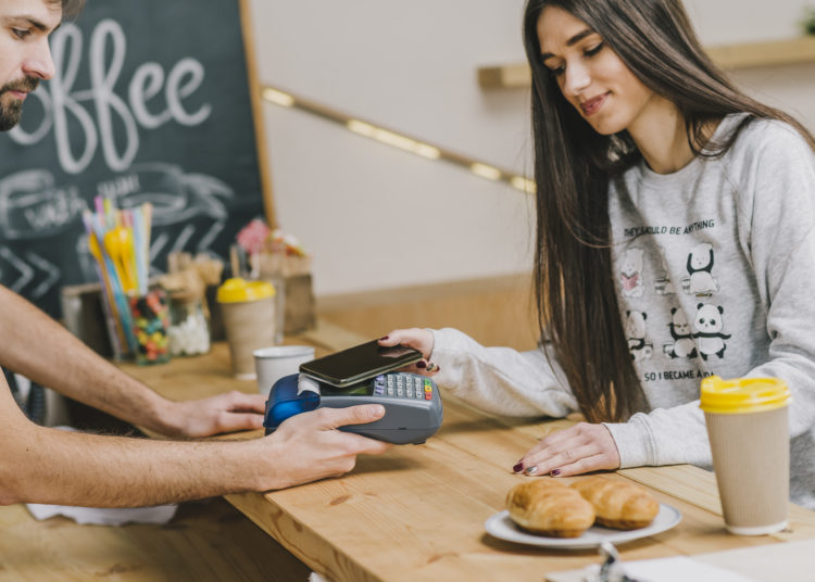Women paying with her phone for muffins