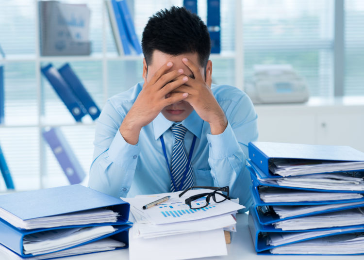 Close-up image of a stressful businessman tired from his work on the foreground