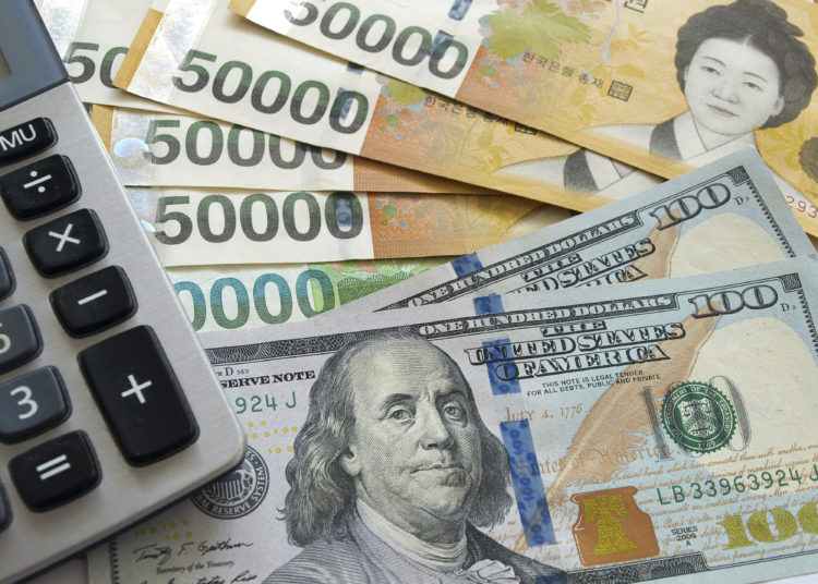 US one hundred dollar and Korean won currency with calculator. Finance business concept.