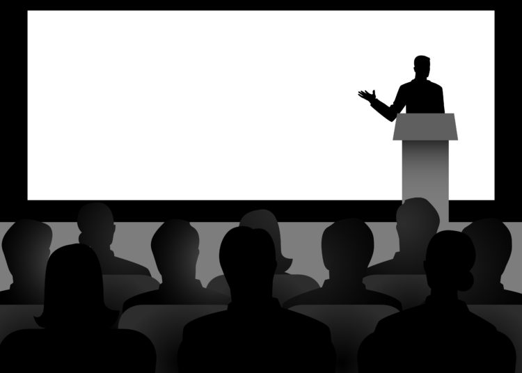 Silhouette illustration of man figure giving a speech on stage with blank big screen as the background