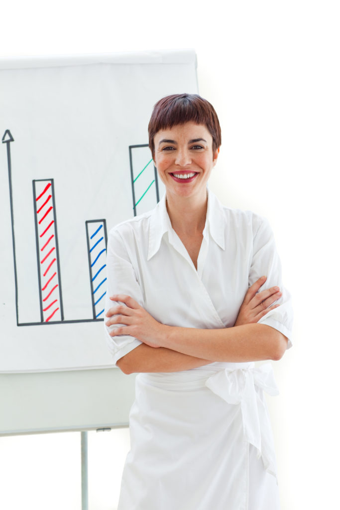 Smiling businesswoman with folded arms in front of a board against a white background