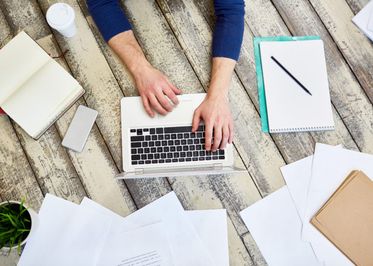 Top view of unrecognizable freelancer working on wooden floor, using laptop computer with documents and business supplies laid out around