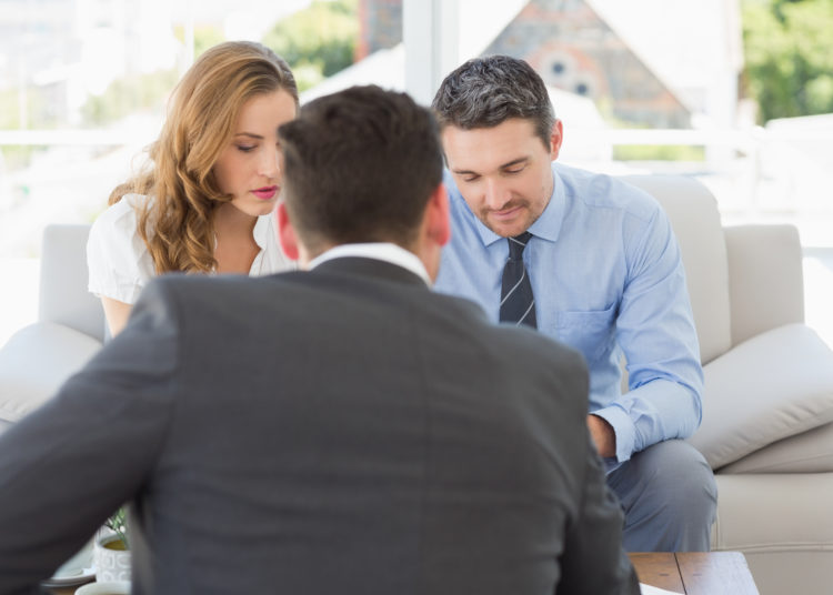 Young couple in meeting with a financial adviser in the living room at home