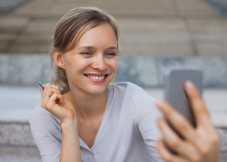 Portrait of cheerful young Caucasian businesswoman taking selfie or making video call with smartphone outdoors. Casual business and communication concept