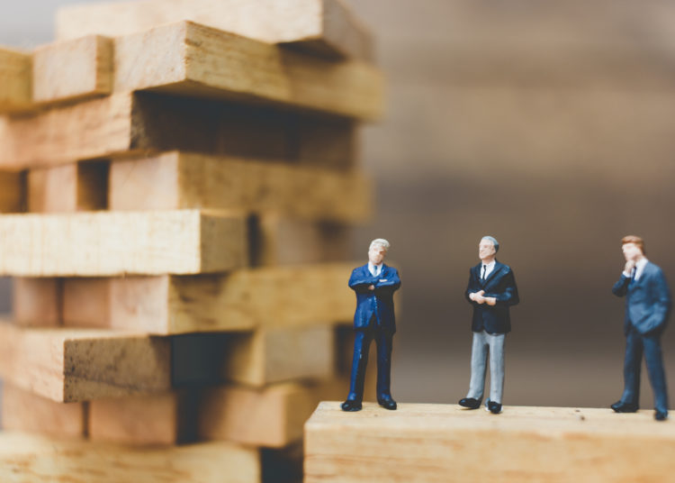Miniature people: Businessman standing on wood block. business success