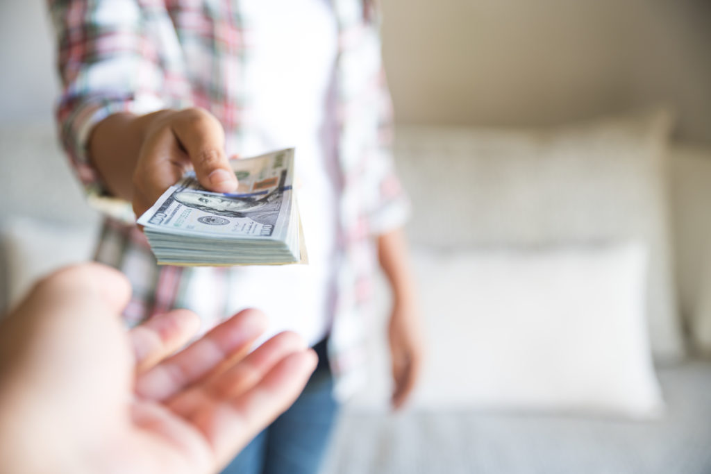 Soft focus on woman hands proposing money us dollar bills to you.