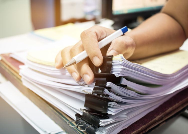 Businessman hands searching nfinished documents stacks of paper files on office desk for report papers, piles of unfinish papers sheet achieves with clips indoor, Document is written, drawn,presented.
