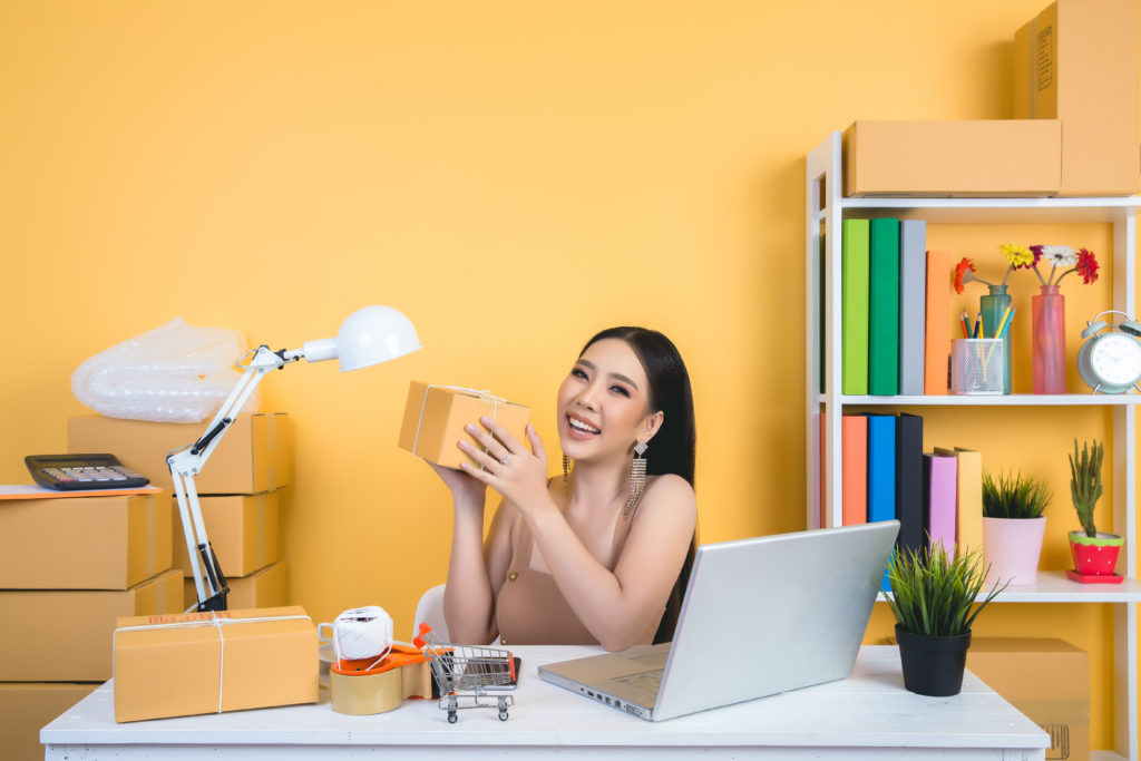 business owner working at home office packaging on background.