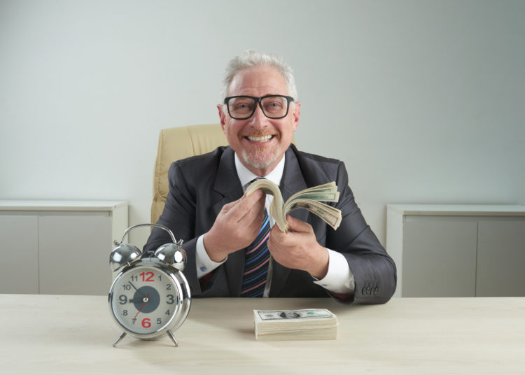 Cheerful senior entrepreneur wearing classical suit and eyeglasses looking at camera with toothy smile while holding bundle of banknotes in hands, alarm clock standing on office desk