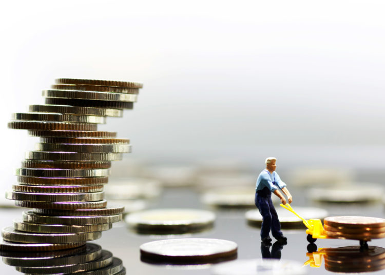 Miniature workers transport coin to the tallest stack , financial,retail,money saving and business concept.